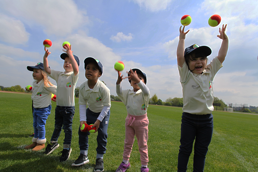 children throwing cricket balls in the air