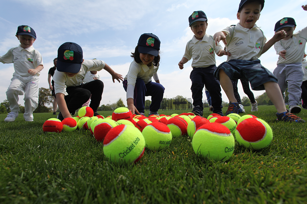 children picking up cricket balls outside