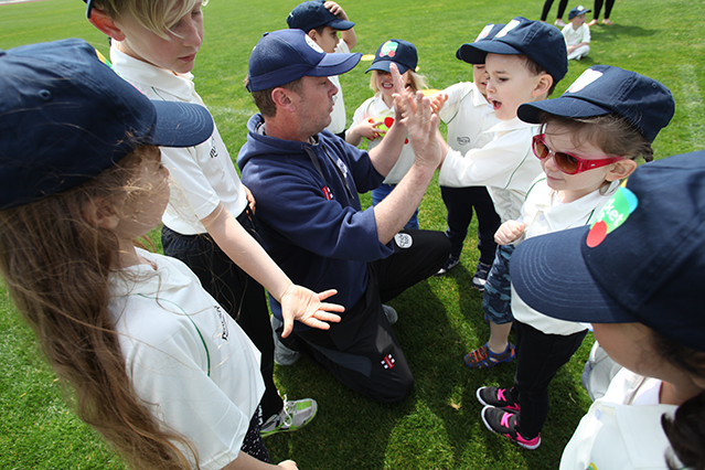 young children high fiving cricket coach