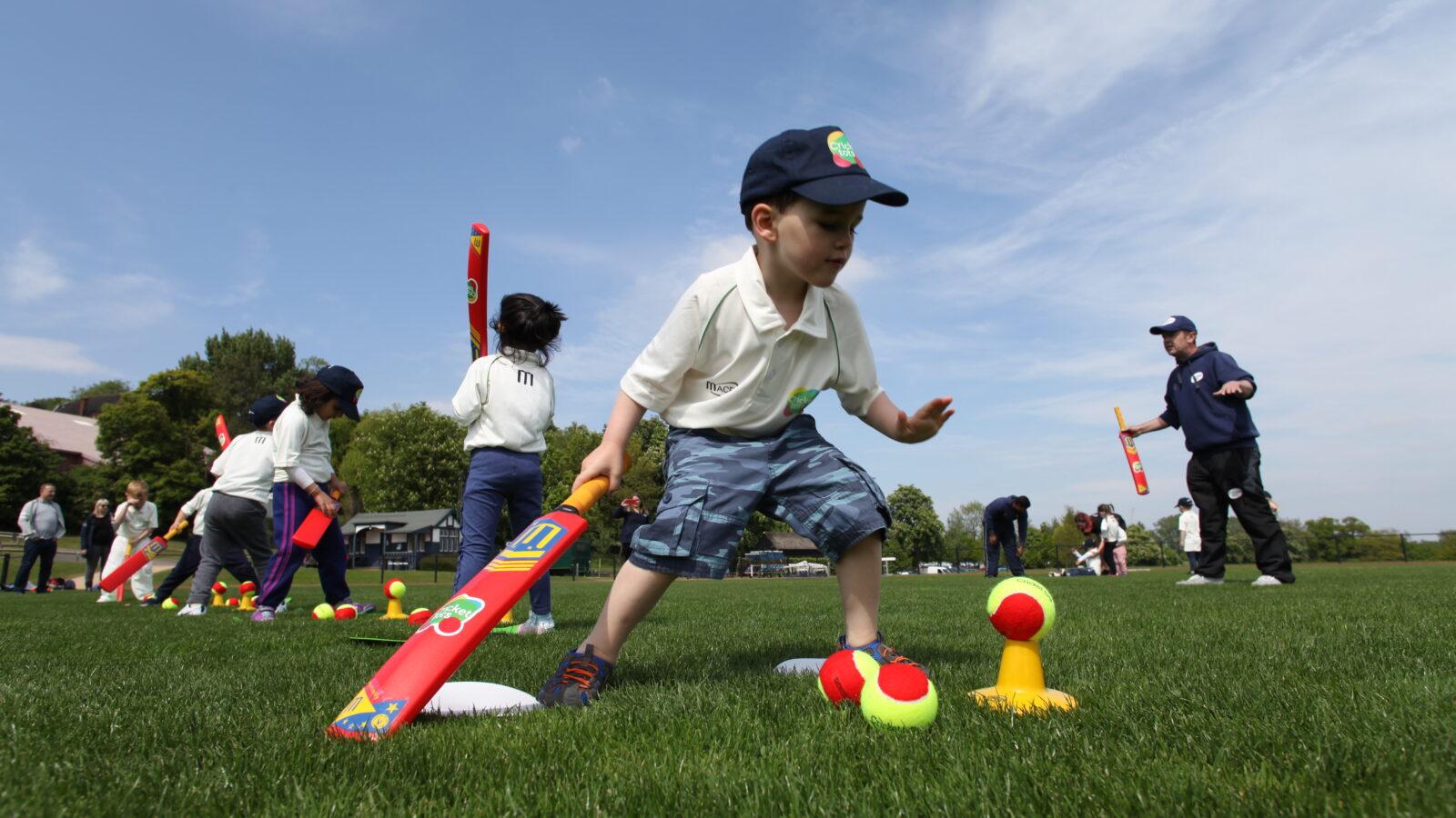 boy holding cricket bat and balancing cricket balls