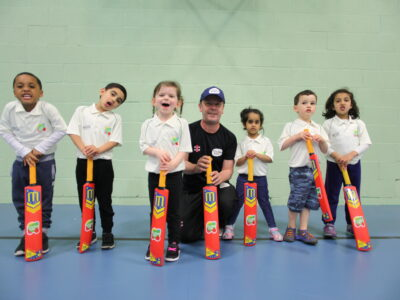 young children holding cricket bats with cricket coach in the middle